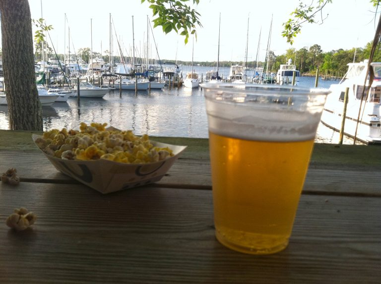 draft beer and popcorn on table overlooking marina