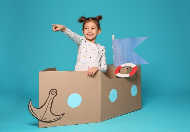 Girl pointing ahead playing in cardboard boat