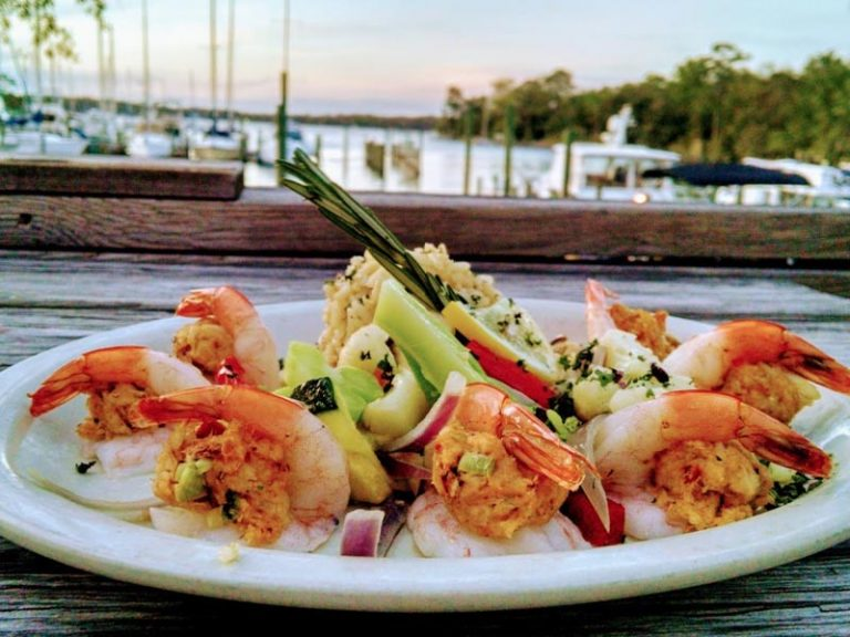 Crab stuffed shrimp dinner on plate overlooking bay